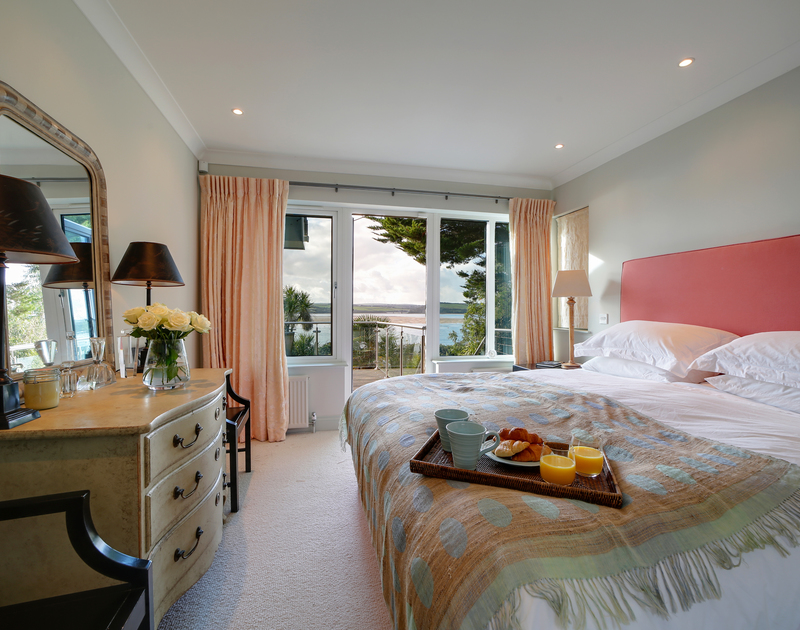 The luxurious master bedroom with Estuary views, access to the deck and ensuite bathroom at Camel Point self catering holiday home in Rock, North Cornwall.