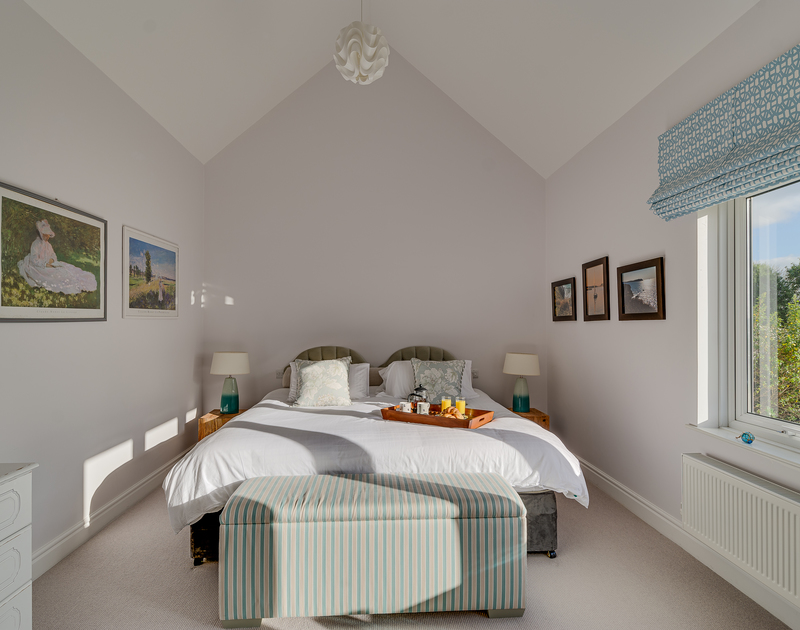 The downstairs bedroom with en-suite and estuary views at Landers Field self catering holiday home in Rock, North Cornwall.