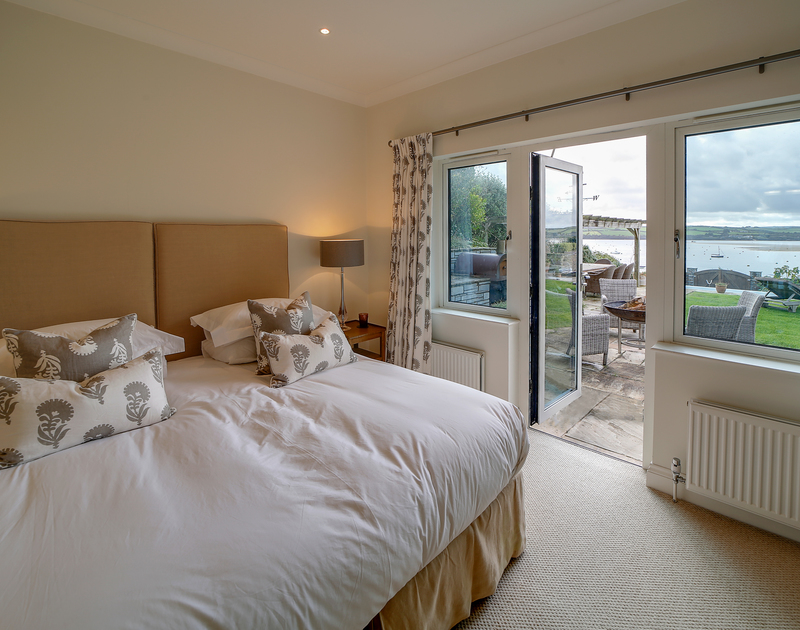 The double bedroom with ensuite, access to the garden and estuary views at Camel Point self catering holiday home in Rock, North Cornwall.