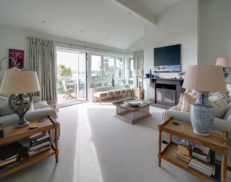 The spacious living room with access to the deck at Camel Point self catering holiday home in Rock, North Cornwall.