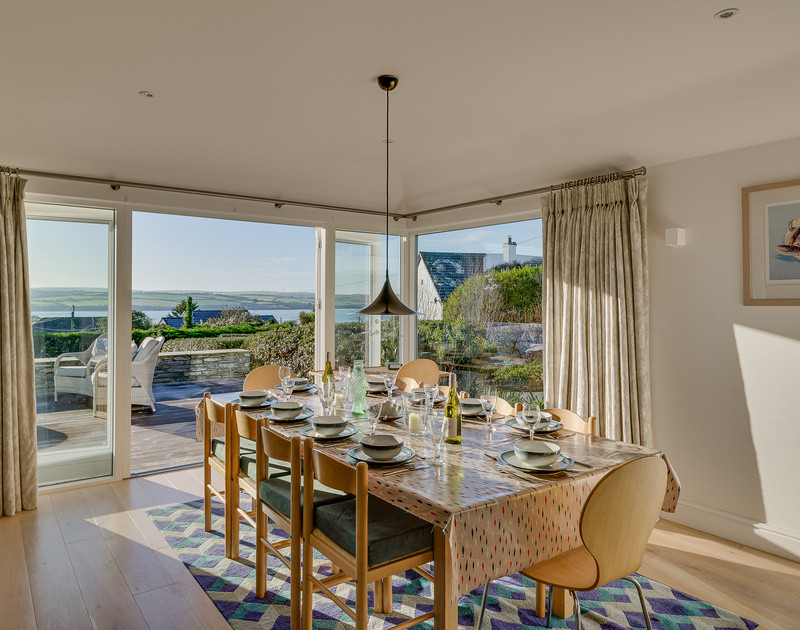 The dining area with amazing view over the Camel Estuary and access to the patio at Landers Field self catering holiday home in Rock, North Cornwall.