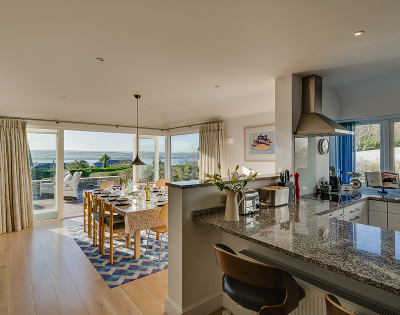 The stylish kitchen and dining area with Camel Estuary views at Landers Field self catering holiday home in Rock, North Cornwall.