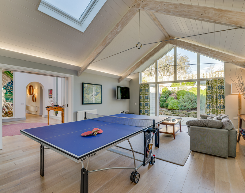 The TV/games room with table tennis table and access to the back garden at pool at Landers Field self catering holiday home in Rock, North Cornwall.