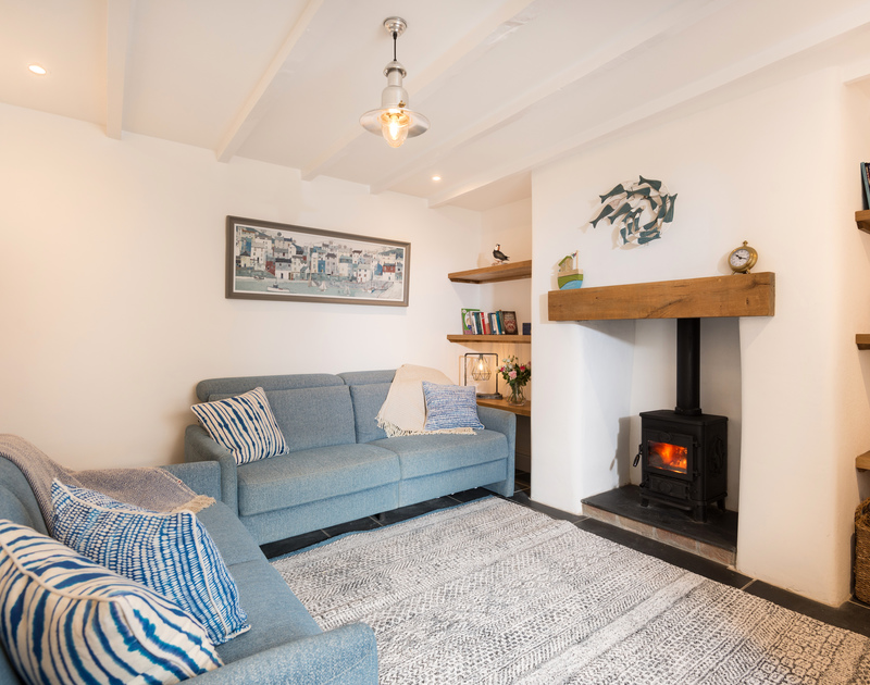 The living room with lovely fire and coastal interiors at Kipper Cottage self catering holiday home in Port Isaac, North Cornwall.