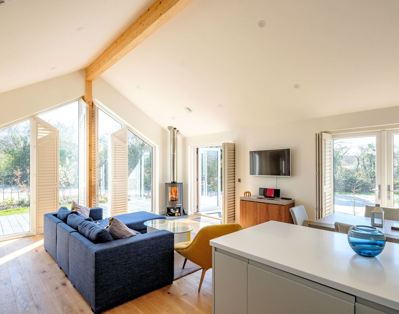 The open plan kitchen, living and dining room with wood burner and access to the deck at Zeath self catering holiday home in Rock, North Cornwall.