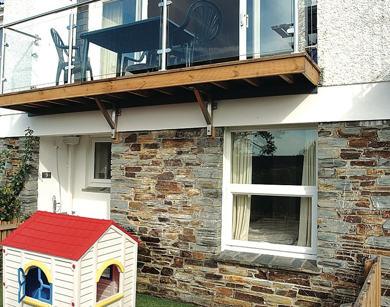 The exterior of Slipway 9, holiday cottage in Rock, Cornwall, with first floor balcony.