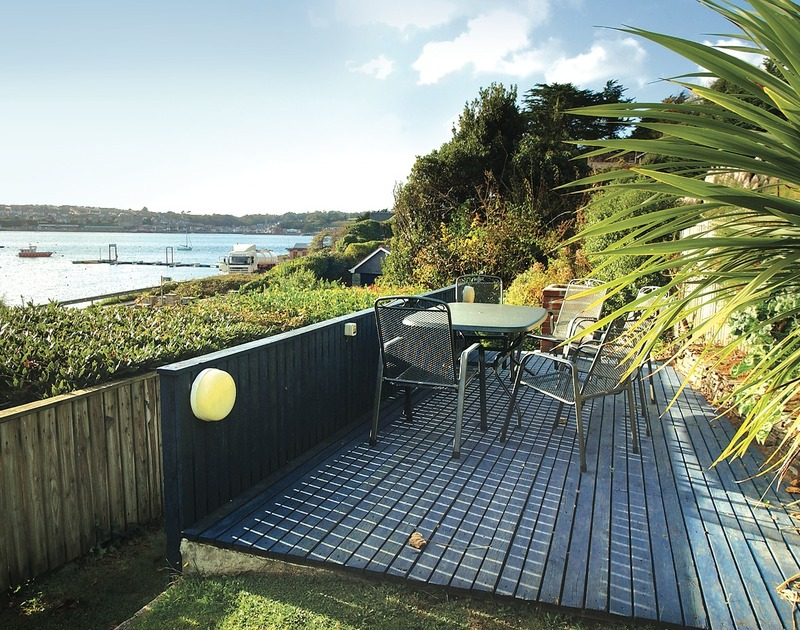 The sheltered, garden decking area with gorgeous Camel Estuary views towards Padstow at The Cottage, a self catering holiday rental in Rock, North Cornwall.