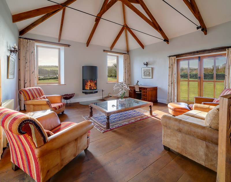 Bright, spacious upstairs sitting room with wood burner and sweeping views across the nature reserve and the gardens