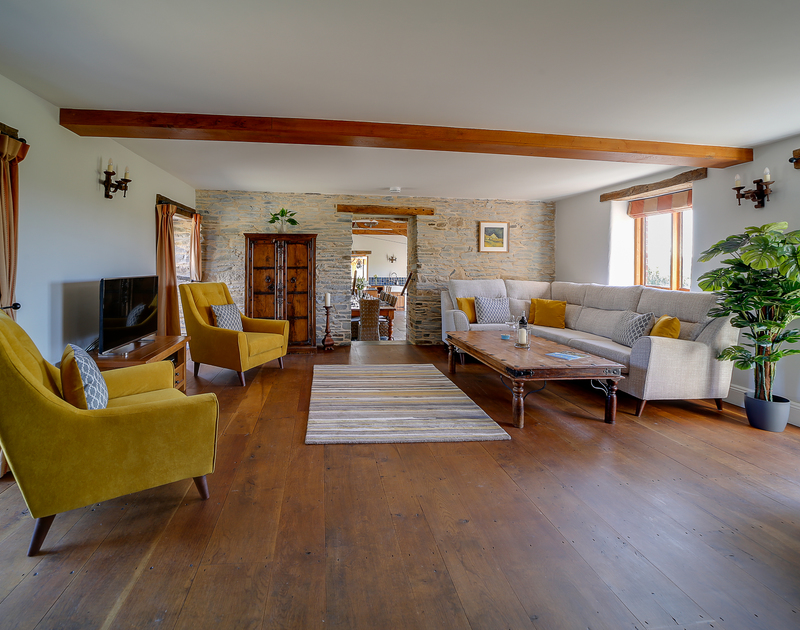 Spacious traditional sitting room with wooden floors and access to outside terrace