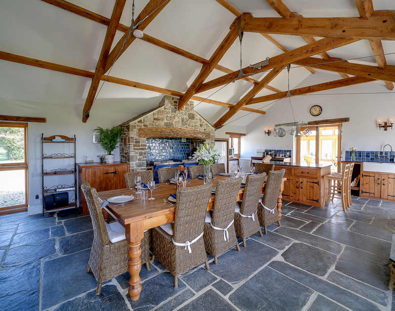 A huge, but cosy and warm country kitchen with slate floors, garden views, an aga and a spacious dining room area