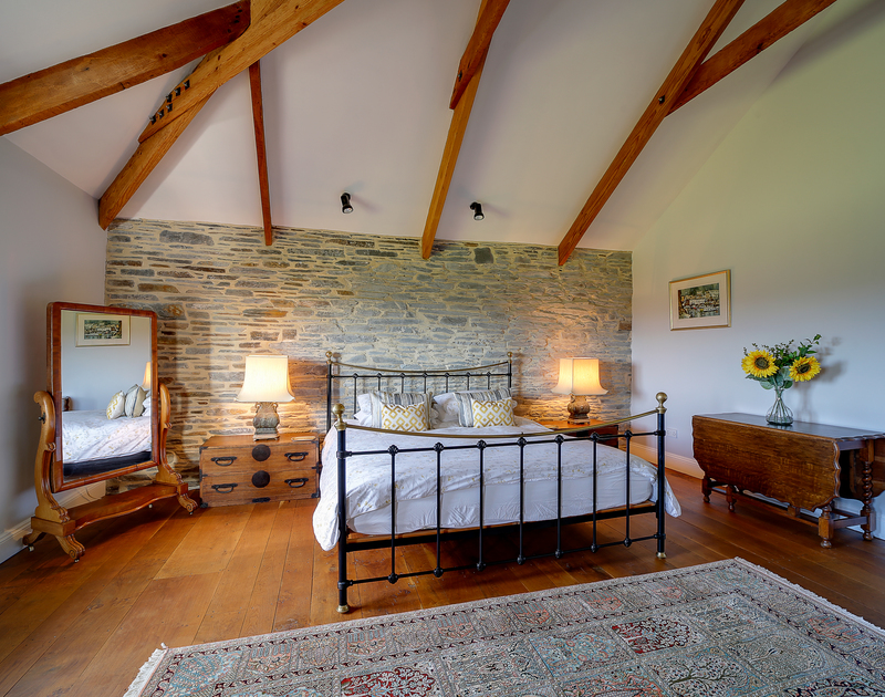 Grand, beautiful upstairs bedroom with a king size iron frame bed, wooden floors and views across the gardens.