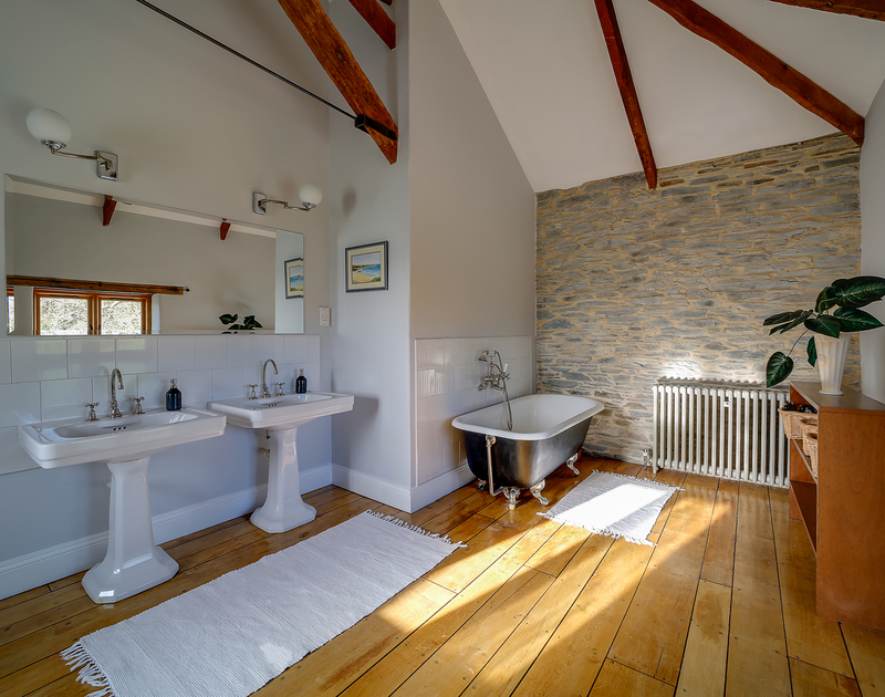 A vast and beautiful bathroom, with traditional features, including a free-standing bath, wooden floors and beams and his and hers sinks.