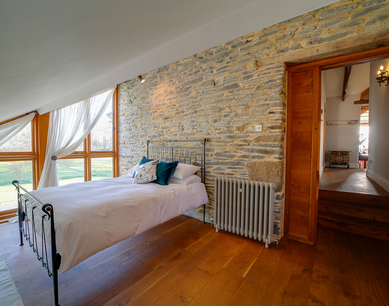 Bright double bedroom, with sloping ceilings and wooden floors, on the second floor of the property.