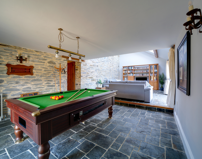 A great family room within the barn, with a games area, including a snooker table, and a reading area filled with books.
