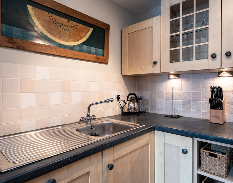 The sink and cupboards of the kitchen at Homelands, in Port Isaac