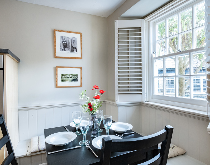A table set for four, two bench seats and two chairs, with a window view of Dolphin Street at the self-catering holiday cottage in Port Isaac