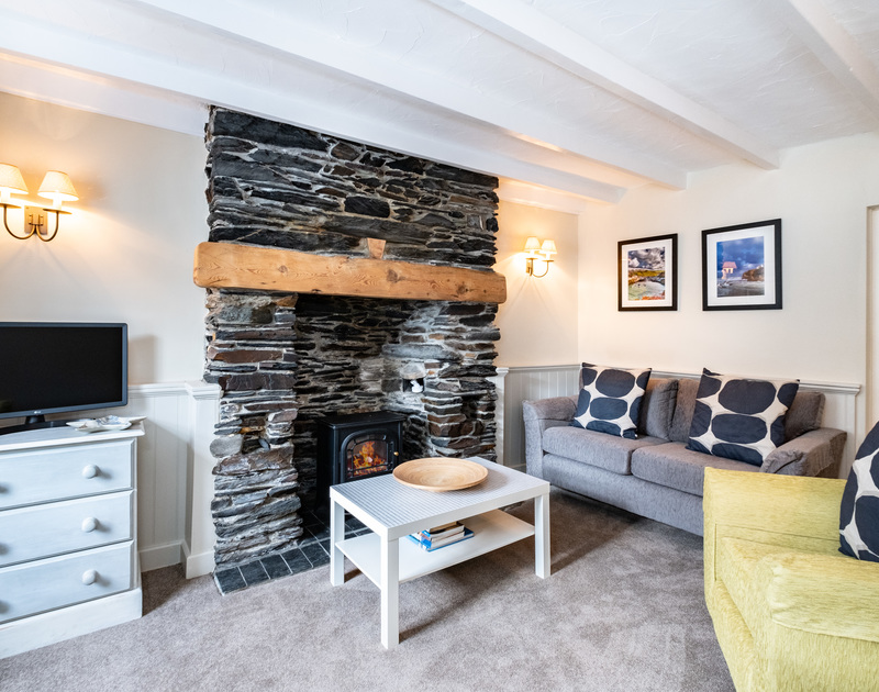 The cosy living room at Homelands with beautiful old stone fireplace and electric fire in Dolphin Street, Port Isaac