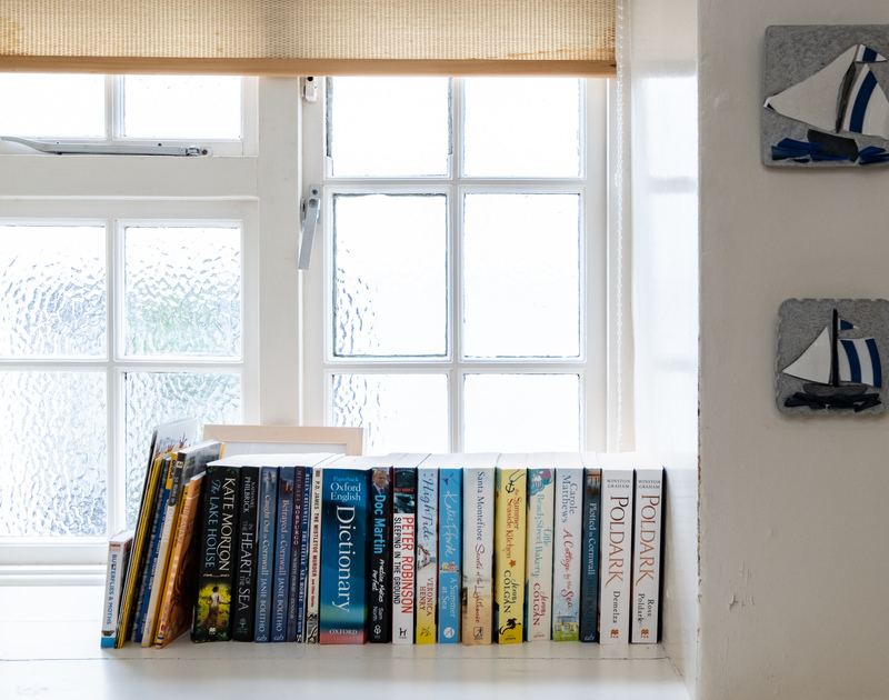 Some books lined up on the windowsill of the the downstairs bathroom in Homelands, Port Isaac