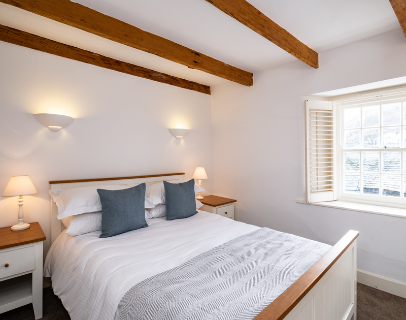 The master bedroom of Homelands in Port Isaac fills with natural light from it's window, with a lovely vantage of Dolphin Street below