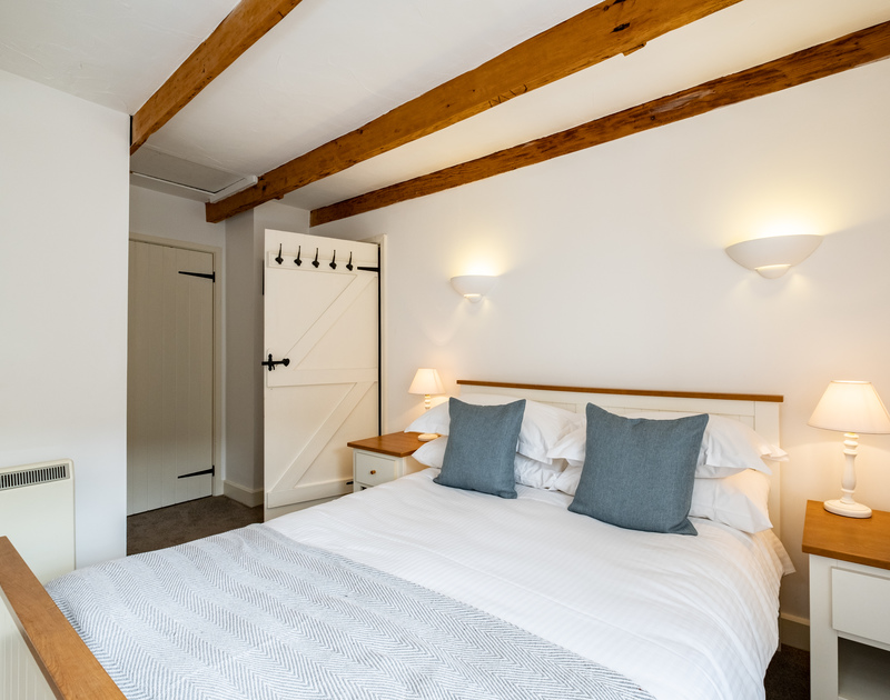 The master-bedroom of Homelands in Port Isaac showing a double bed, door with hooks behind and bedside tables and lamps on either side of the bed