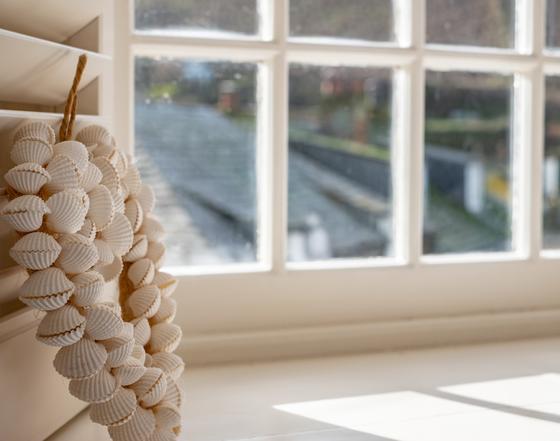 An artistic shot of a sea-shell decoration in the windowsill of Homelands, Port Isaac
