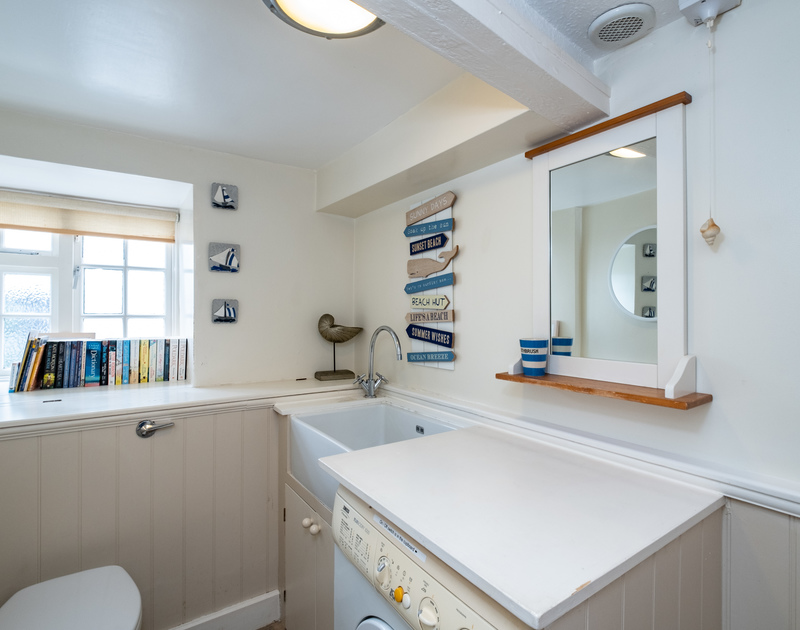 A loo, sink and washing machine in the downstairs bathroom/utility room of Homelands, self-catering holiday cottage in Port Isaac