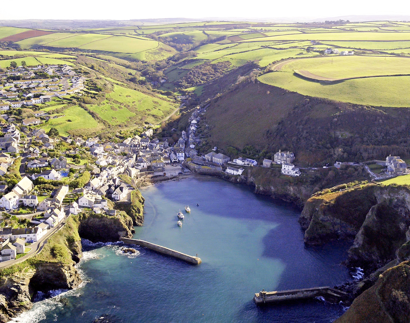 Aerial shot of Port Isaac harbour in the late afternoon sun, complete with fishing boats