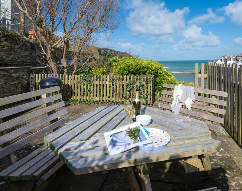 Enjoy a sunny BBQ while looking out across the picturesque harbour at Scuppers terraced garden, Port Isaac