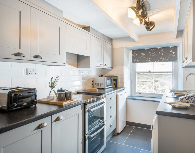 The light-filled kitchen of Scuppers with its well equipped cupboards, to make a comfortable stay in Port Isaac