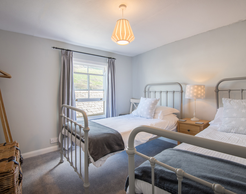 The twin bedroom decorated in gentle grey tones at Scuppers, Port Isaac