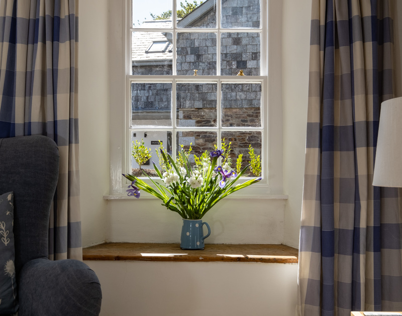 Lovely fresh flowers dress the livingroom windowsill of Stokes Cottage as it fills with afternoon sun