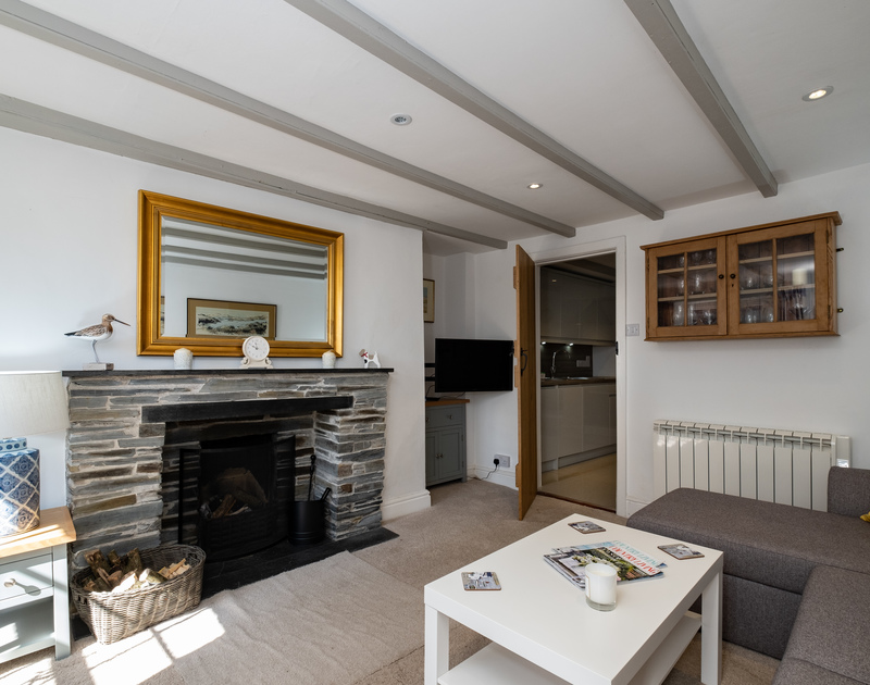 The cosy living room at Stokes Cottage, complete with a charming slate fireplace