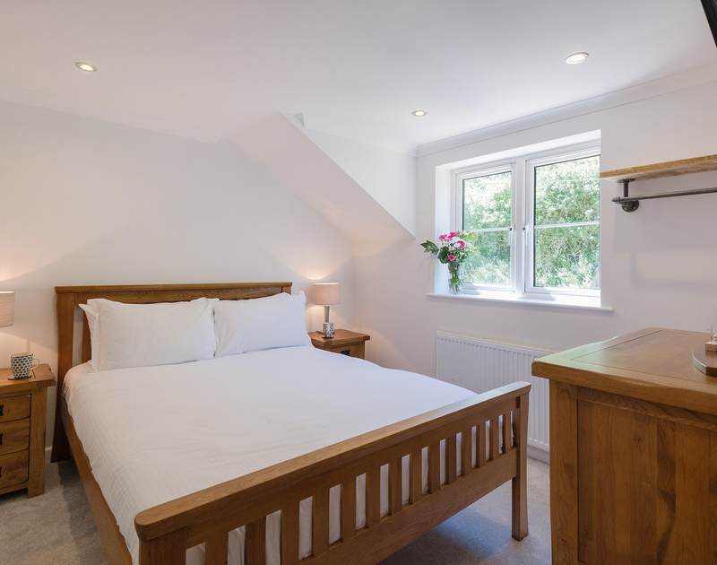 The master bedroom of Stop Tide, with it's king-sized bed and wall-mounted TV for a perfect lie-in...someone just needs to bring up the tea!