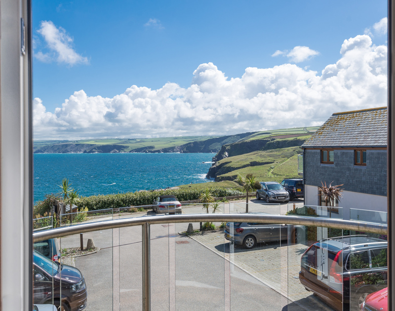 Ocean Breeze's living-room balcony looking across the sea to the neighbouring cliffs of Port Gaverne & beyond...