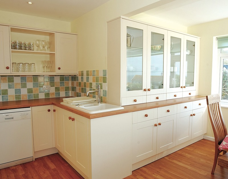 The kitchen sink and attractive fitted cupboards in the kitchen at Trevic, a self catering holiday bungalow in Polzeath, Cornwall.
