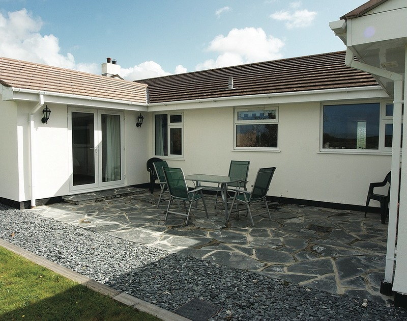 The slate patio at Medway, a holiday house to rent at Rock, Cornwall, with outdoor furniture.