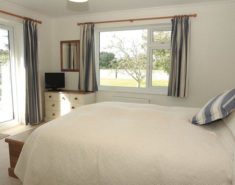 A double bedroom at Medway, a holiday house in Rock, Cornwall, with kingsize bed and doors to the terrace.