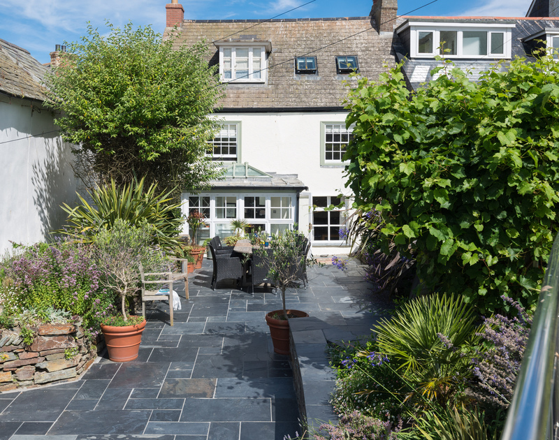 The view of the sunny patio in the enclosed garden of Trevan House, as you stand in the garden above