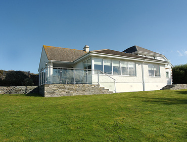 The exterior view of Higher Crawallis, a holiday rental near Daymer Bay, with its lawned garden.