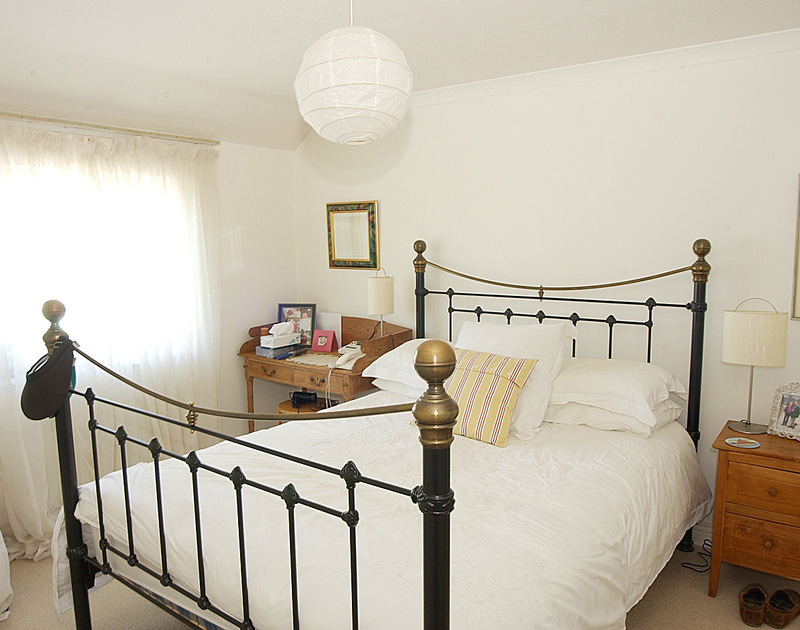 One of the two attractive king size beds in Marbeachow, a self catering holiday house to rent in Tredrizzick, near Rock in Cornwall.
