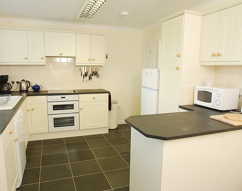The cream and black, well-equipped kitchen at Medway, self-catering holiday house at Rock, Cornwall