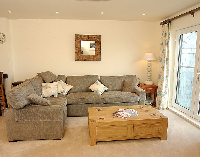 Comfortable corner sofa in the sitting room at Rock Lobster, a self catering holiday house to rent in Port Isaac, Cornwall.