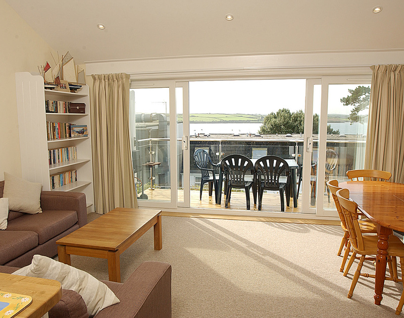The open plan living room of Slipway 9, holiday cottage in Rock, Cornwall, with seaview from the balcony.