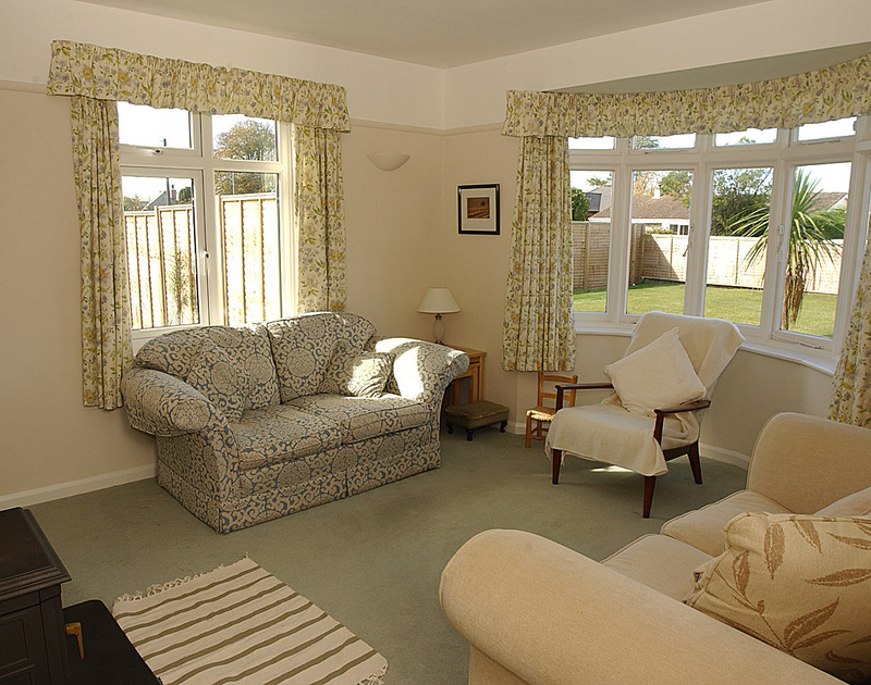 The lounge with lovely bay window at Trevian, a self catering holiday house to rent in Rock, Cornwall.