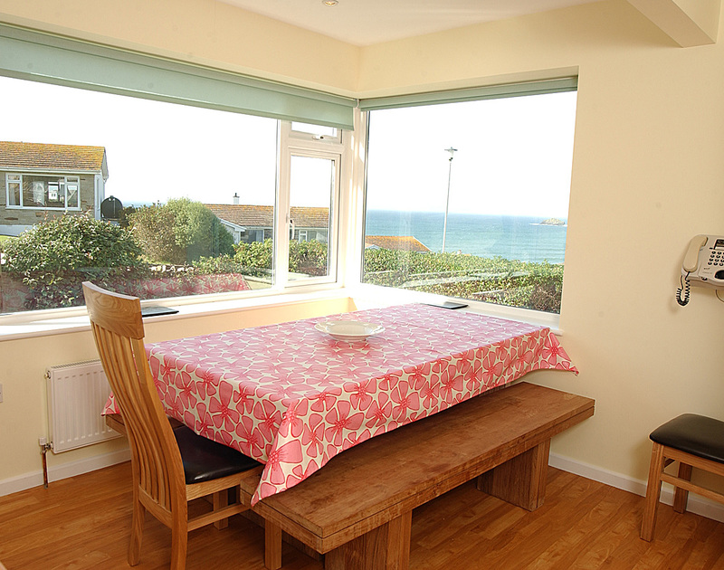 The light-filled dining room with superb sea views from Trevic,a holiday bungalow set in an elevated position overlooking Polzeath, North Cornwall.
