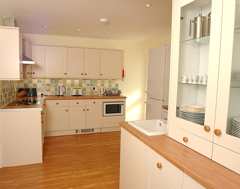 The modern, well equipped kitchen at Trevic, a seaside holiday rental on Tristram cliff at Polzeath in Cornwall.