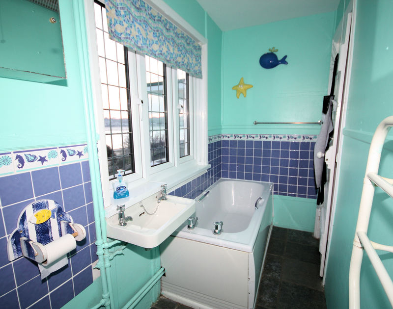 The compact, colourful bathroom of Cocklebar, holiday house in Rock, Cornwall, with its Camel Estuary views.