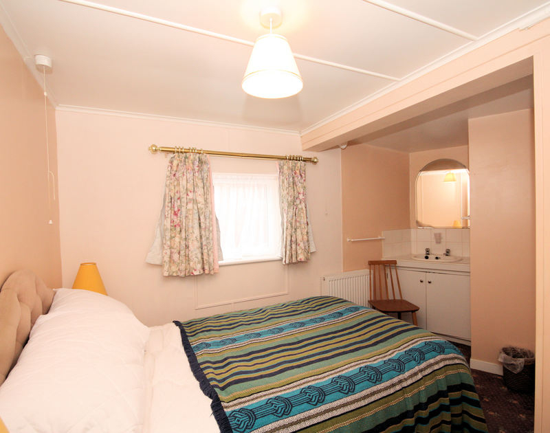 The double bedroom with ensuite shower-room at Malindi, a holiday house with sea views at Polzeath, Cornwall