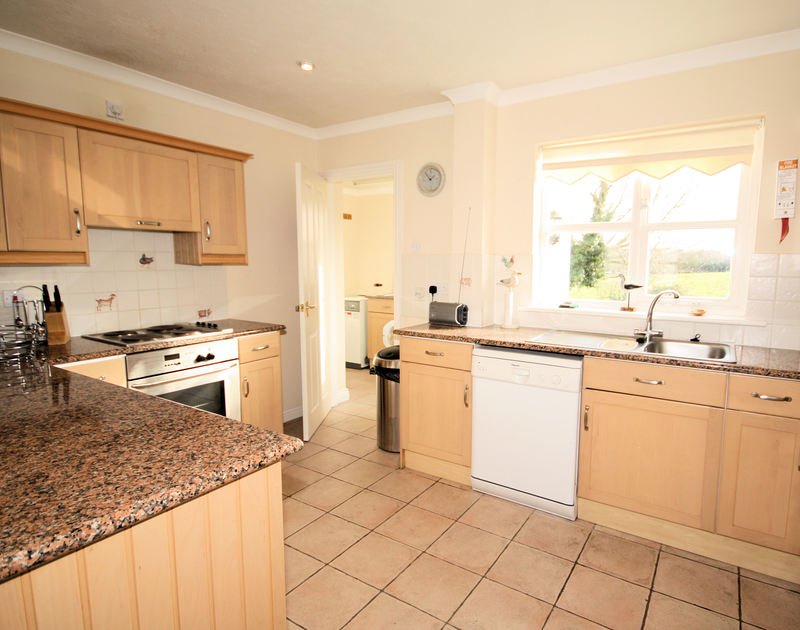 The bright kitchen with additional utility room at Tresow, a self catering holiday house to rent in Tredrizzick near Rock in North Cornwall.