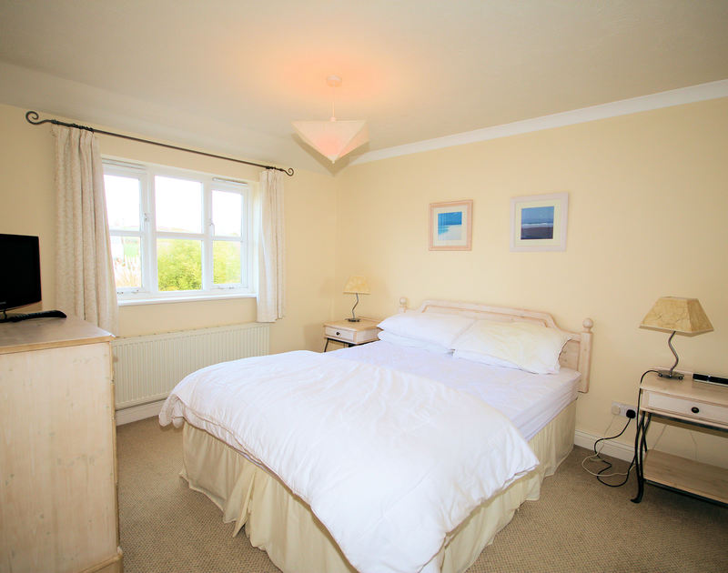 The comfortable king size bedroom in Tresow, a self catering holiday house to rent in the peaceful hamlet of Tredrizzick, Rock, Cornwall.
